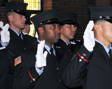 Marland Lawrence (c), a Navy Vet connected by the GI Go Fund to his job as a Newark Firefighter and to his college education, takes his oath into the dept