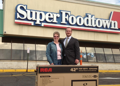 """Top Cashier Doris Yurcho, left, poses with her new RCA 42"""" Television with GI Go Fund Deputy Director Alex Manis (right), in front of her Super Foodtown in Wall, NJ."""