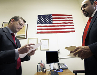 French Consul-General Bertrand Lortholary (left) reads a letter from Anne Marie Crespo addressed to Mr. Wilkins and his Daughter, Carol, in the GI Go Fund Veterans Office in Newark City Hall with Executive Director Jack Fanous (right).
