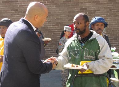 """Newark Mayor Cory Booker listens to a homeless veteran's story at the """"Stand Down of North Jersey"""" on Saturday, October 13, 2012 in Newark, NJ."""