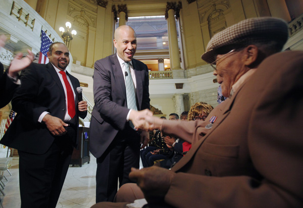 GI Go Fund Executive Director Jack Fanous (left) and Newark Mayor Cory Booker (center) present to Army Corporal Willie Wilkins (right) of Newark the dog tags he lost while serving in France in WWII, along with the NJ Meritorious Service Medal.
