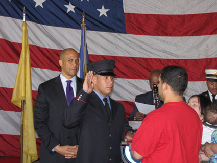 Newark Mayor Cory A. Booker (l) swears in newest Newark Firefighter Joseph Carpio, who set to deploy to Afghanistan on 9/12/12 as a member of the Marine Corps Reserve